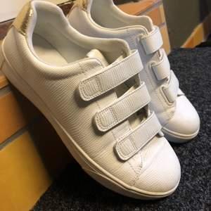 Använda vita sneakers med carborrespännen, fint skick.