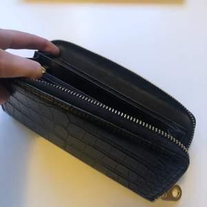 Svart plånbok i fake skinn med guldig dragkedja. Bara använd en gång, precis som ny. Många fack där man kan ha över 10 kort, man får även platta med sin mobil i den. Säljer då den inte används. Frakt 44kr