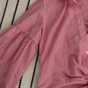 En gullig somrig röd och vit randig blus med puffärmar. Köppt på bik bok i storlek s. Aldrig använd så i fint skick
