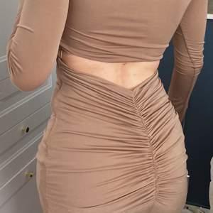 En så fin gyllenbrun klänning från Nelly. Öppen rygg och även ribbad. Dragkedjor på sidorna och väldigt skön!! Använd 2-3 gånger!! XS, normal i storleken. 🦋