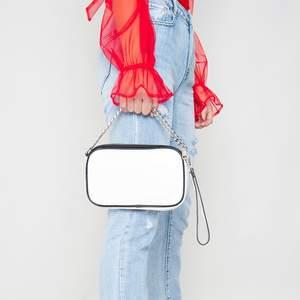 Vit hand och axelväska, dvs du kan ta bort långa kedjan och använda som handväska.. den har tre fack och dragkedja på toppen. Vit med svarta detaljer runt och silverkedjor.