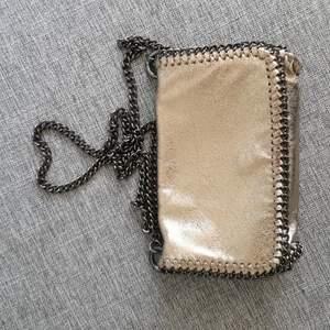 Fin modern väska från ginatricot i färgen guld! Aldrig använd så helt ny!
