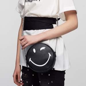 Smiley World x Pull and Bear väska för 50kr. 18cm i diameter och har en liten defekt (se sista bilden). Möts upp i Gävle eller fraktar för 66kr.
