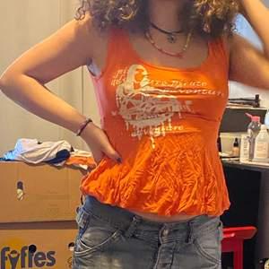 Ett orange linne med en liten kjol och text på. Köparen står för frakten