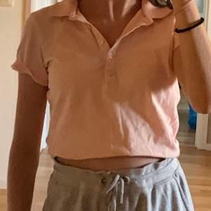 En fin ljus rosa polo tröja som är köpt från sail racing.