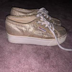 Superga skor i en guldskimrig färg med högre sula. Använd ett fåtal gånger så är i hyfsat nyskick. Bekväma att gå i trots att de är lite högre i sulan. Hör av er vid frågor:)