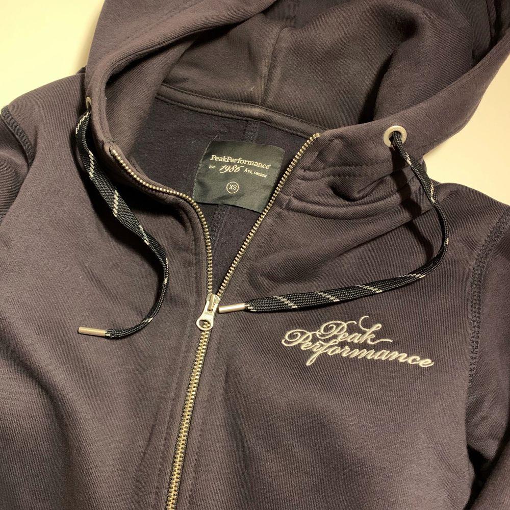 Mörkblå zip hoodie från Peak Performance i storlek XS. Använd fåtal gånger och är i nyskick. 299 kr + frakt. Huvtröjor & Träningströjor.