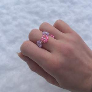 Fin pärlring med rosa och lila blommor runtom, handgjord, går att få i flera olika färger/storlekar. Skriv privat så kan jag anpassa ringarna:) Tar swish, pris kan diskuteras.
