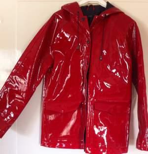 Oanvänd klarröd plastglans-regnjacka från topshop. En aning stel i materialet. Storlek 38