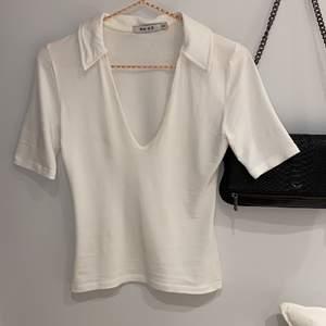 Superfin T-shirt med krage och djup v-ring från NAKD. Storleken är XXS enligt lappen men skulle mer säga att den passar xs/s. Endast använd 2 ggr