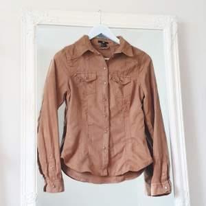 Färg: brun.  Strl: 36.   Snygg skjort-blus från H&M, i mockaimitation. Använd vid ett par tillfällen, men i fint begagnat skick. Figursydd och detaljer av fickor framtill. Sluts igen med knappar framtill. Fraktkostnad tillkommer, betalning via swish