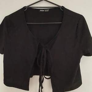 Svart T-shirt från SheIn i storlek S med två snörningar i mitten, stor i storleken, aldrig använd utan glömde skicka tillbaka