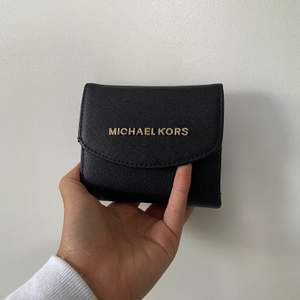 liten smidig plånbok med guld detaljer. I skinn.