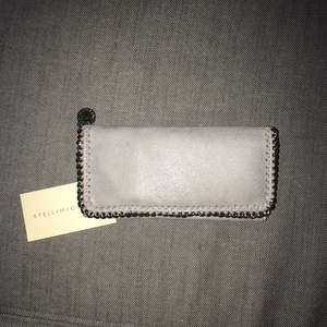 Stella McCartney plånbok grått på utsidan lite rosa på insidan. Som ny.  A kopia, extremt bra kvalite exakt som äkta