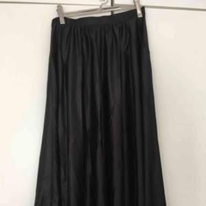 Kjol i glansigt tyg, fickor och skärphällor