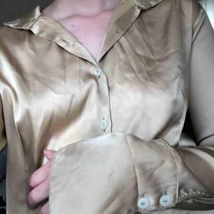 Guldig skjorta med långa armar.   100% polyester  Vid köp kan vi antingen mötas upp i centrala Stockholm eller så betalar köparen frakten.