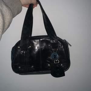 """En jätte fin svart mini purse i """"skinn""""! I jättebra skick och använd några gånger!💗 Säljer då den inte kommer till användning längre! Jätte 2000s stil! Kan mötas upp och frakta!💗"""