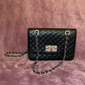En svart mini handväska med kedje remmar av Don Donna. Sen använd väska i väldigt gott skick. Inga synliga skråmor eller repor. Ett stort fack och ett litet extra fack. Från 2000-talet ✨