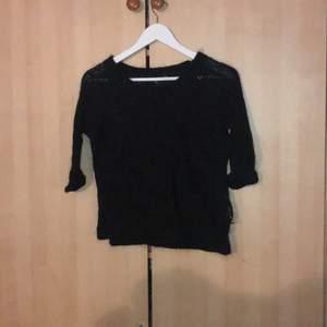 En stickad tröja med trekvartslånga armar, slit längst ned. Storlek M