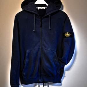 Stone Island-hoodie som passar både M och L. Den här modellen har två stycken framfickor som har Dragkedja vilket jag insett är ett måste nu när jag haft det. Tröjan är i bra skick och är självklart äkta. Det finns en CLG-kod/QR-kod i tröjan som visar att den är äkta som efter förfrågan kan skickas. Tröjan är i en väldigt mjuk mörkblå och passar till nästan alla kläder! Kan mötas upp och frakta :D
