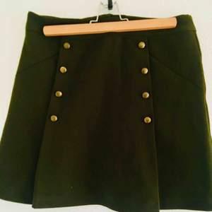 Grön kjol med knappar framtill, knappt använd, lätt utsvängd nertill