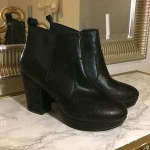 Svarta fakeläder boots. Klack ca 10 cm platå ca 2 cm. Använda endast vid ett tillfälle, nyskick. Storlek 40. Märke Voxshoes Stockholm