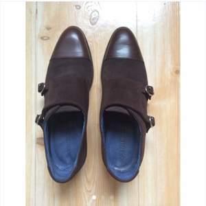 Oanvända monkstraps från J.Lindeberg. Skorna är i storlekar 40 i mörkbrun mocka och läder. Nypris 2000 och mitt pris är 650kr.