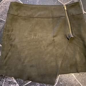 Mörkgrön kjol i mockatyg, använd 1 gång. Man drar igenom en knapp på insidan men när den köptes var hålet nästan för stort för knappen enligt mig. Går ju att byta till större knapp, men funkar även som den är nu. Fint skick!