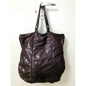 Handväska i svart glittrande mjuk tyg. Går att bära på två olika sätt. Har 3 små fickor på insidan. Tyget från ett av handtagen är slitet (se bild ovan), men det syns inte när man håller den runt armen/axel.