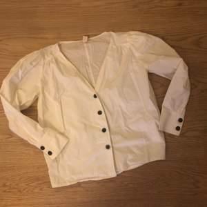 Vit bomullsblus/skjorta från HM trend, mörkbruna knappar fram och på ärm. Fint skick!