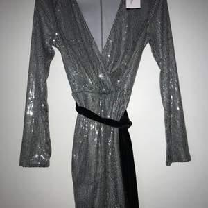 Oanvänd klänning från nelly.com med etikett på. Klänningen är i storlek 34 och säljes eftersom att den inte kommer till användning. I midjan finns äcen ett svart sammetsskärp som även kan tas bort och bytas ut till ett annat. Klänningen är glittrig och är en perfekt fest klänning. Färgen på klänningen är grå/ grön. Ordpris: 500kr