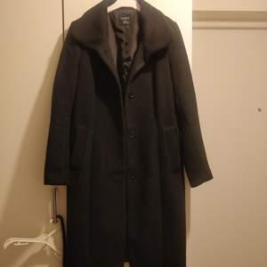 En svart ullkappa med skärp från Lindex i storlek 38. Köpt för 800 kr. 85% polyester, 15% ull