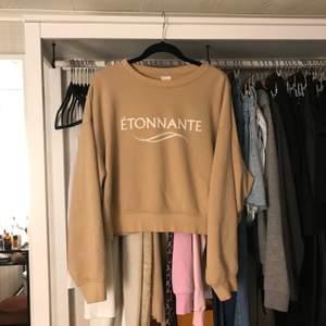 """En beige hoodie från H&M som har texten """"ÉTONNANTE"""" på sig. Hoodien är helt som ny! Köpare står för frakt💗 (kan även mötas upp)"""