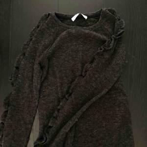 Så mjuk tröja från mango i en mörkgrå färg. Jättefina volanger på armarna och helt oanvänd (bara testad)