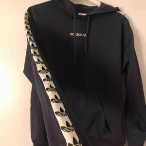 Marinblå Adidas TNT tape sleeve hoodie, köpt från ASOS. Stor i storleken