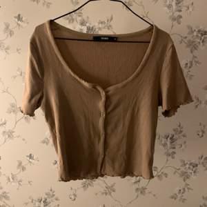 En beige t-shirt från BikBok i färgen beige. Tröjan är i storlek M