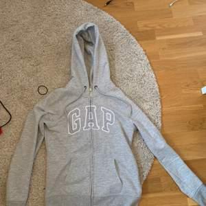 En snygg grå hoodie med dragkedja ifrån GAP. Mycket fint skick och inte använd många gånger alls pga för liten för mig. Köparen står för frakten🥰