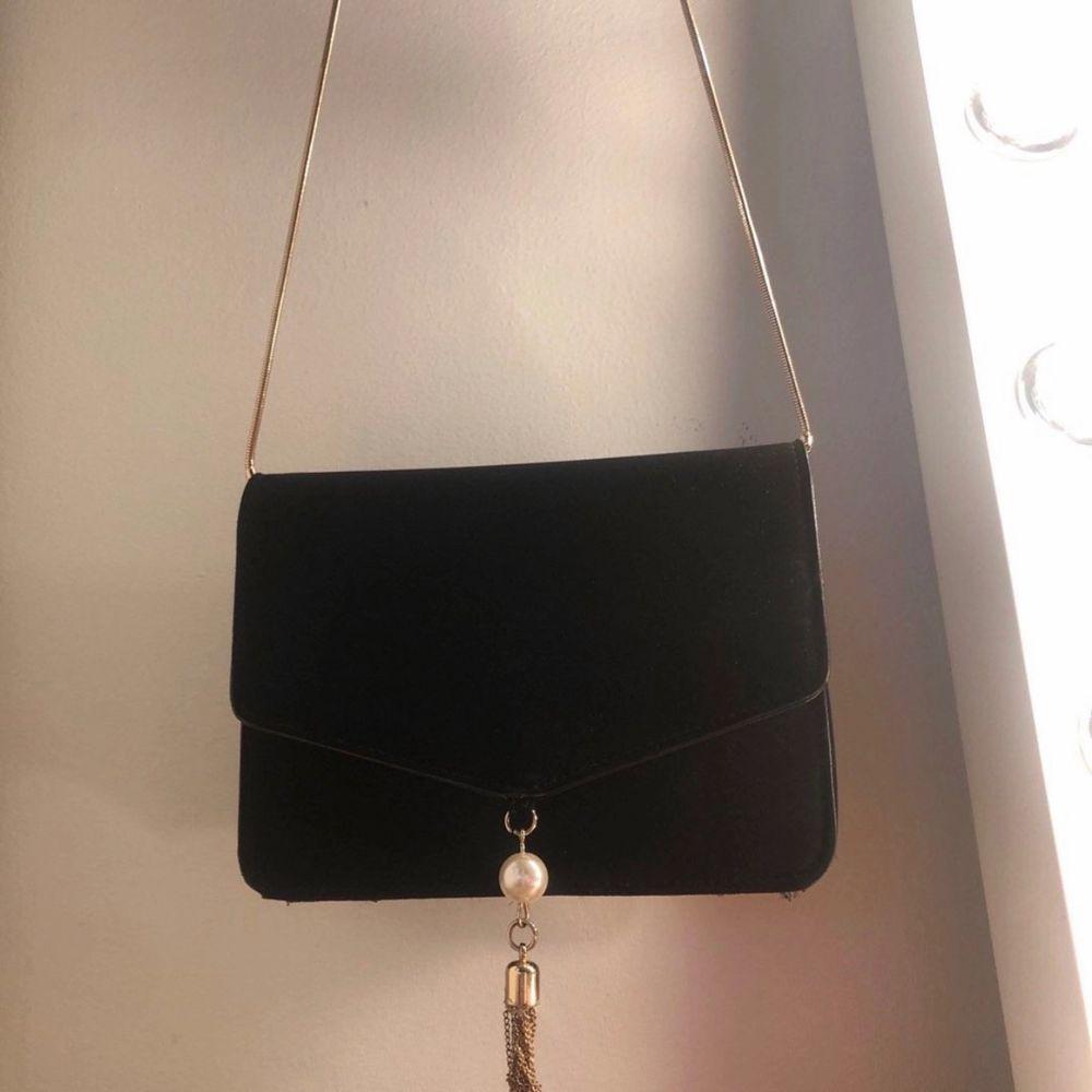 Fin liten svart axelväska med guld färgar band och detaljer. Accessoarer.