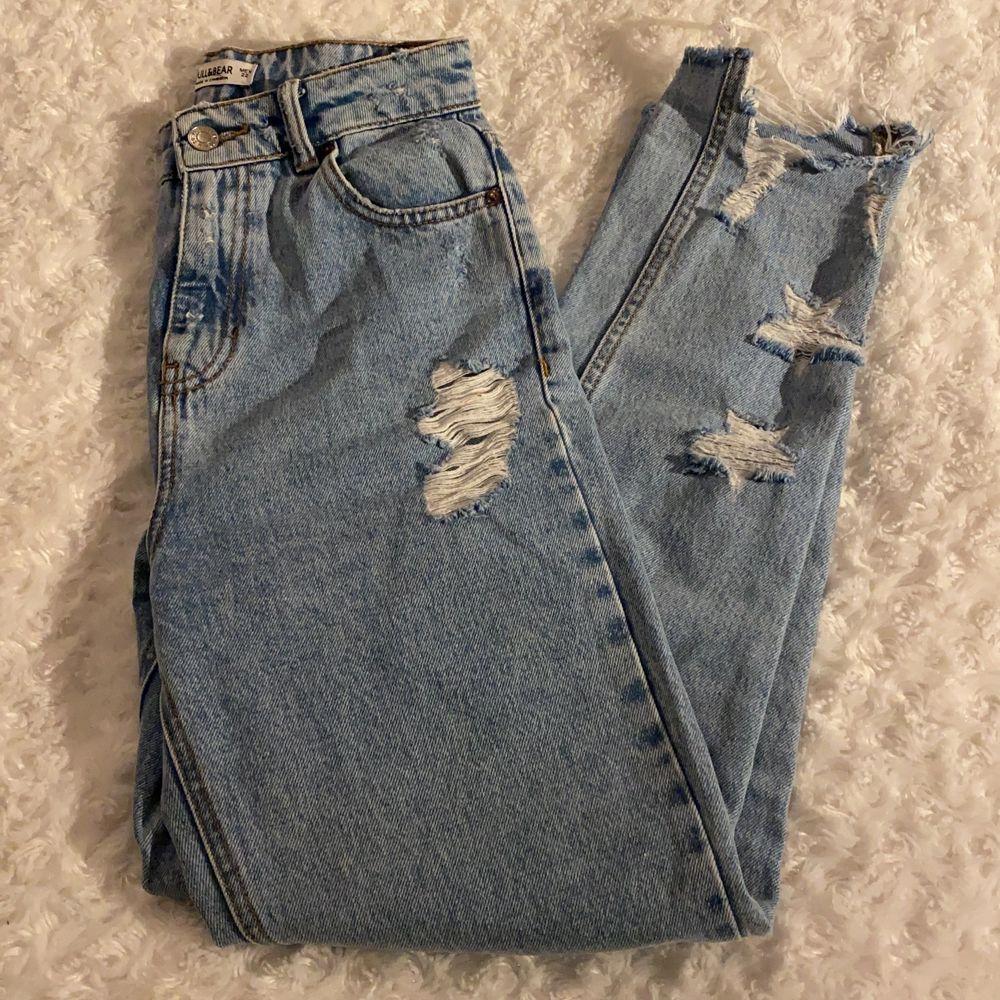 Slitna jeans från Pull&Bear i storlek 32 💙💙 Jeansen har mom-fit och har fina slitningar i form av stjärnor ⭐️ Dem är i mycket fint skick och är använda max 1 gång! Samfraktar gärna med andra plagg och betalning sker via Swish <33. Jeans & Byxor.