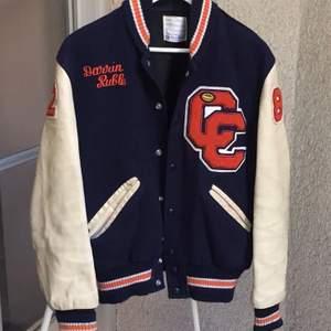 Intressekoll på min versity jacket.                                    Marin blå baseballjacka med inslag av orangea detaljer. Normal passform på mig som vanligtvis är M. Köpt här på plick för omkring 2000kr. ✌🏻