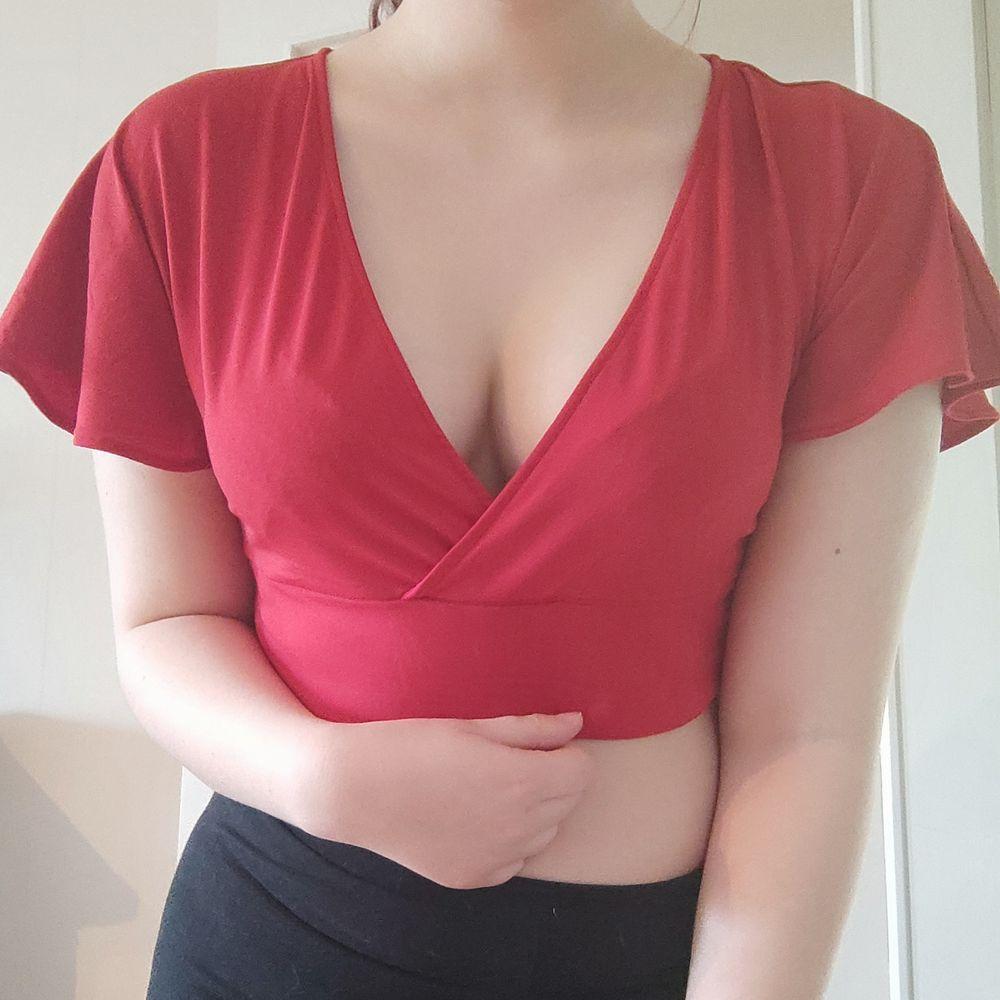 En kort röd topp med korta flare sleeves i så gott som oanvänt skick. Toppen har öppen rygg med knytning. Passar medium -large. . Toppar.