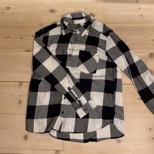 """Fräsh svart och vit rutig skjorta med framficka och svarta sömmar.🖤🤍  Bra skick. Bekväm, snygg och cool. Material (mjukt och skönt) 100% bomull. DM vid intresse/frågor/fler bilder.❣️ (Det kan du göra här under där det står """"kontakta""""). Avhämtning på Södermalm eller frakt till självkostnadspris.:)"""