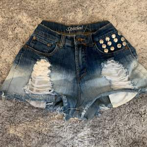 Denim shorts with metal details on front pocket and a cros on the back pocket. They are ripped in from and have very large pockets