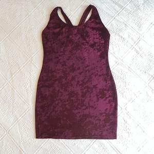 Vintage fodralklänning från sena 90-talet i kort modell med korsrygg. Krossad velour med stretchig kvalitet i vinröd/bordeaux. Fin och djup lyster i tyget. Mäter 84 cm från axel till kjolkant. Sparsamt använd.