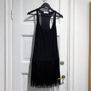 Selected Femme, stl 34. Svart klänning med fransar i Charleston / Great Gatsby stil. Använd en gång. Dragkedja i sidan. Hel och ren. Snören vid ringningen kan justera ringningen. Fransar från höfterna, klänningen fortsätter under 💕
