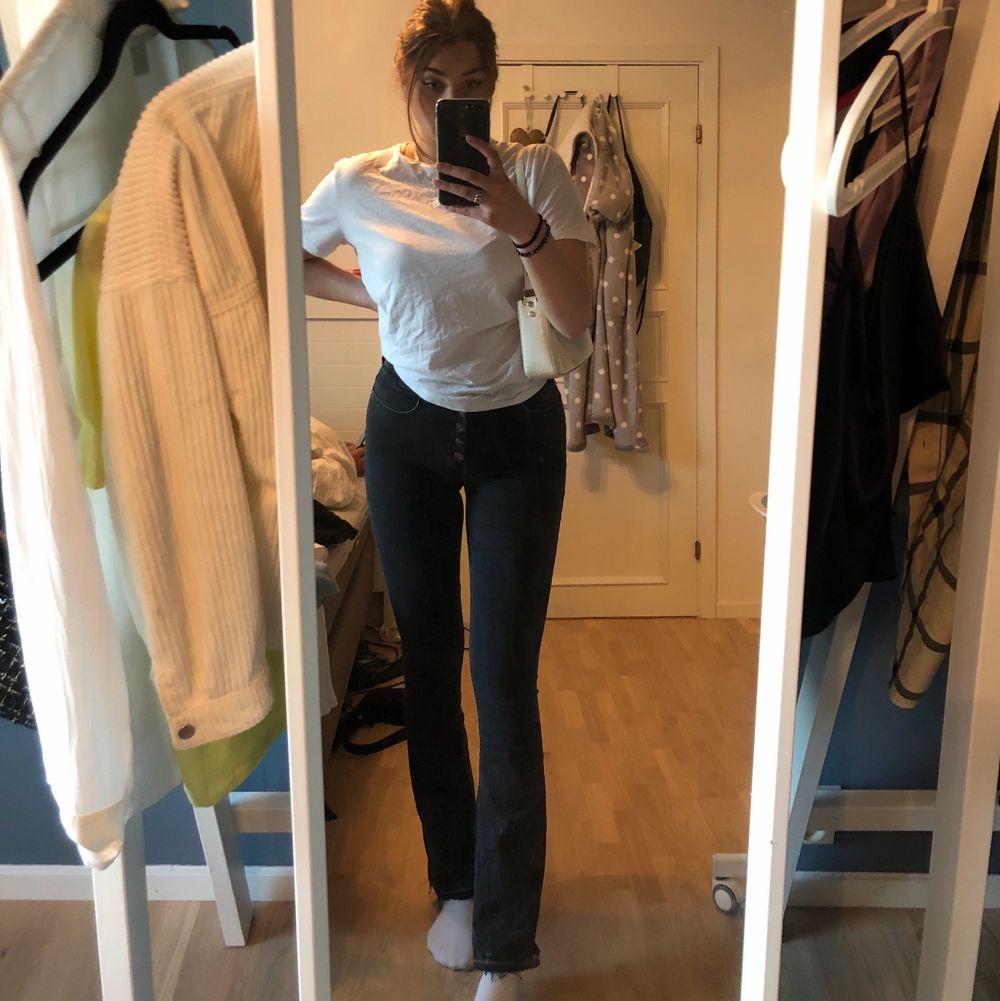 Säljer dessa grå jeans i flare modell / bootcut som har knappar! Långa, passar mig som är 173. Så fina men används tyvärr knappt av mig längre, skriv vid frågor💛. Jeans & Byxor.