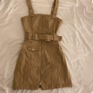 En beige/brun jeans klänning från H&M storlek 36. Aldrig använd och kanske därför kan komma till användning hos någon annan! Köparen står för frakten, kan även mötas upp i Borlänge✨