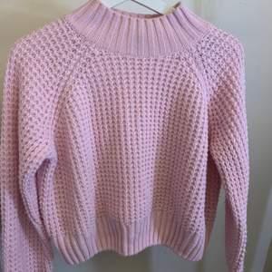 En ljusrosa stickad tröja med halvpolo.