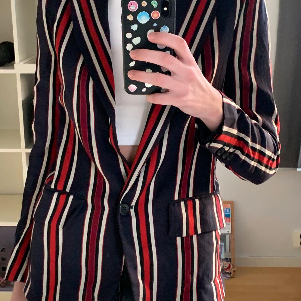 Randig blazer från H&M endast använd en gång. Mörkblå med röda och vita ränder. . Kostymer.