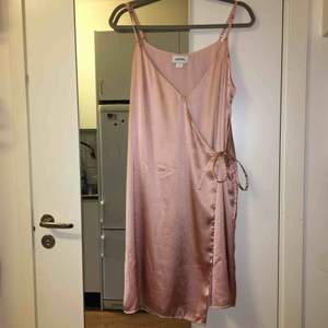 Omlottklänning från Monki med tunna band. 100% polyester. Använd endast vid ett tillfälle.  Kan mötas upp alt. skicka.